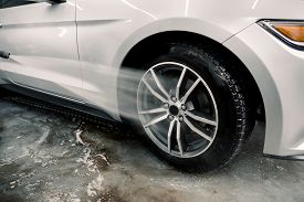 Washing A Car By Hand, Car Detailing. Close Up Image Of The Process Of Cleaning The Car Wheels With