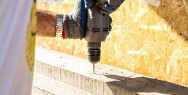 A Worker Drills A Hole In A Wooden Bar With A Drill On Wooden. Wooden Bar Drilling With An Electric