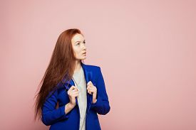A Redhead Girl Is On The Pink Background. A Thoughtful Redhead Girl Is On The Pink Background. A Gir