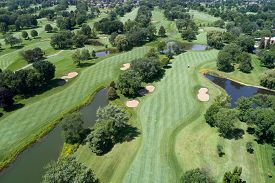 Aerial view of a golf course with fairways, sand traps and greens in a suburban setting.