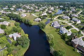 Aerial view of a tree-lined, upscale suburban neighborhood with various ponds in summer.