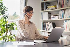 Young business woman using laptop and talking on cellphone in office. Smiling businesswoman in happy conversation on mobile phone. Cheerful girl sitting at table and working from home in smart working