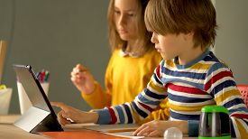 Distance Learning Of School Subjects For Daughter And Son At Home. Mother Controls The Process Of Ho