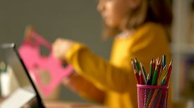 Distance Education Of Children At Home. A Schoolgirl Performs A Creative Task Out Of Paper. In The F