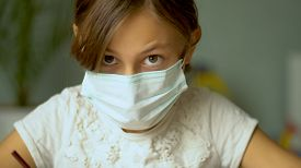 Home Training During The Quarantine Period Of The Coronavirus Covid19. A Girl In A Medical Protectiv