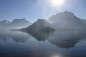 Annecy Lake And Mountains With Reflections Of Sun And Flare In Sky And Water