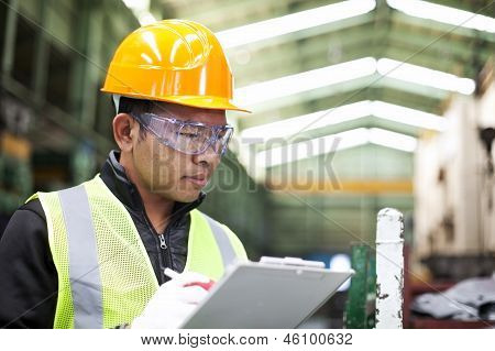 Factory Worker Writing On Clipboard