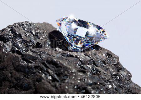 Foto de um único corte diamante em um pedaço de carvão contra um fundo liso.