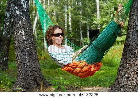 Young woman in dark sunglasses lies in hammock outdoors and works on notebook