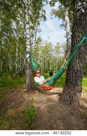 Young barefooted woman in dark sunglasses lies in hammock outdoors with notebook