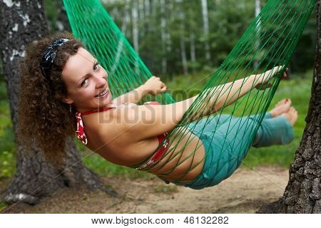 Young smiling barefooted woman swings in hammock, head turned back