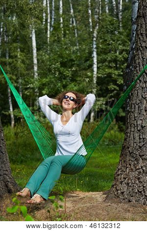 Young smiling woman in dark sunglasses sits in hammock, turning his face to the sun and putting her hands behind her head