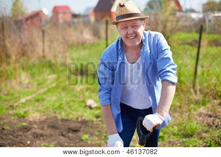Image of male farmer looking at camer while working in the garden