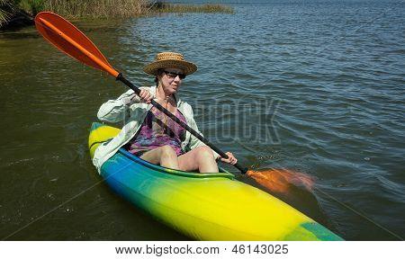 Mujer madura disfruta remando pacífica en su Kayak