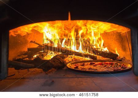 traditional Italian pizza wood oven with raw pizza and large fire in the background poster