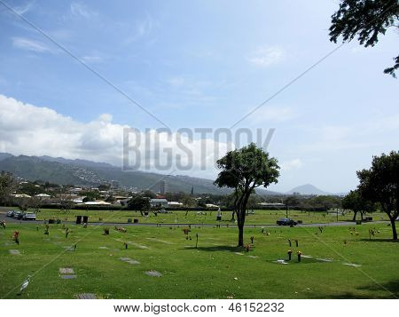 Graveyard With Flat Graves, A White Bird, Statues, And Cars Next To Diamond Head Crater