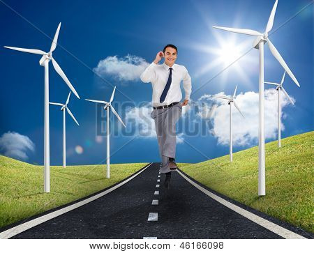 Businessman running on a road next to windmills and green landscape