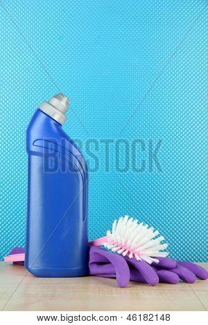 Cleaner bottle, toilet brush and gloves on blue background