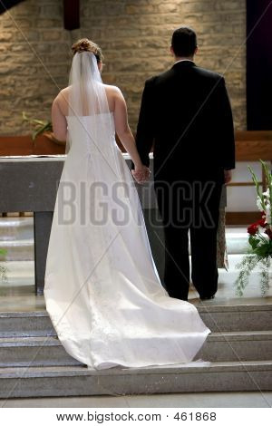 Young Couple Holding Hands At Altar On Wedding Day