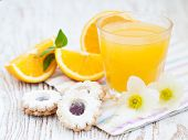 Orange juice spring blossom and cookies on a wooden background poster