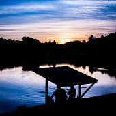 fisherman fishing at sunset on a like poster