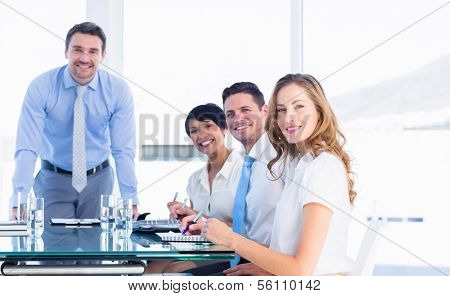 Smartly dressed young executives around conference table in office