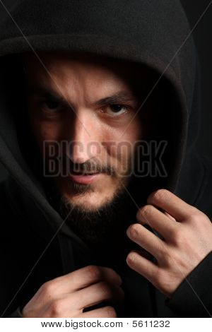 Portrait of young man hiding in black hood