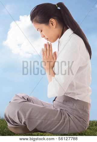 Businesswoman sitting in lotus pose against cloudy sky background