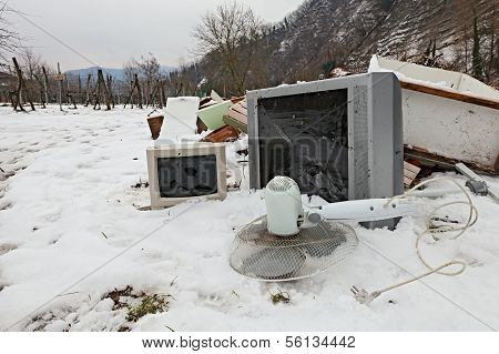electronic waste and electrical appliance abandoned in the snow - illegal waste dump in the countryside poster