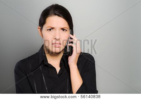Puzzled Woman Chatting On Her Mobile