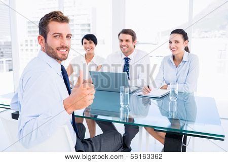 Portrait of an executive gesturing thumbs up with recruiters during a job interview at office