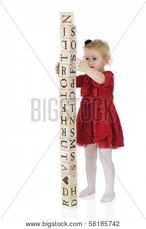 An adorable, dressed up preschool girl steadying rustic alphabet blocks that she's stacked into a tower taller than herself.  On a white background.