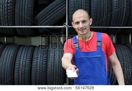 A smiling mechanic in a garage  hands over his business card.