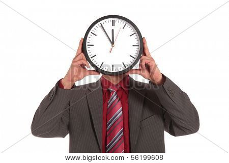 A businessman holding a clock that shows the eleventh hour right in front of his face. All on white background.