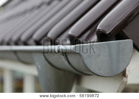 Close-up shot of a eavestrough at a standard roof.