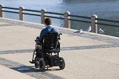 disabled person in wheelchair outdoors poster