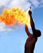 Circus fire-eater blowing a large flame from his mouth poster