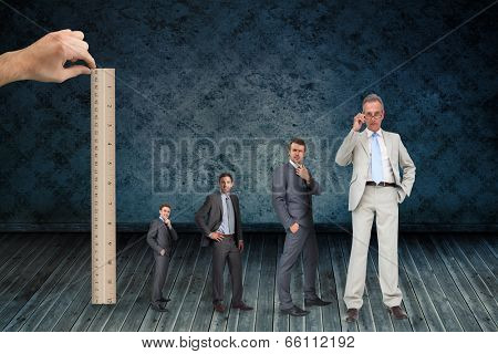 Composite image of hand measuring stages of businessmans life with ruler against dark grimy room