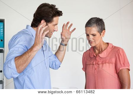 Angry businessman shouting at employee in the office