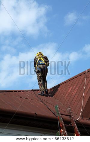 Construction worker wearing safety harness and safety line working on a roof