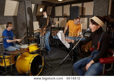 rock band is working in studio. vocalist girl is singing with text of song in the her hand