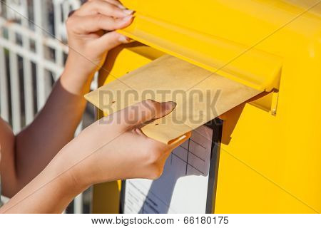 Woman Inserting Envelope In Mailbox