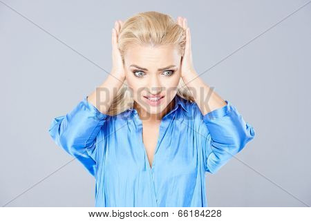 Desperate woman holding her hands to her ears and staring at the floor with an agonised wide eyed look  on grey