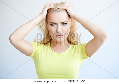 Beautiful young woman with a puzzled expression standing frowning at the camera with her hands to her hair as she tries to understand what is happening