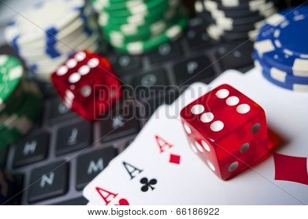 Casino chips, cards and dices stacking on a laptop