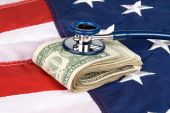 A pile of cash on an American flag with a stethoscope on the money inferring anything from medical costs to economic health and financial stability. poster