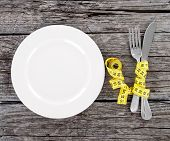 plate with a knife and fork wrapped in measuring tape on a wooden background. diet concept poster