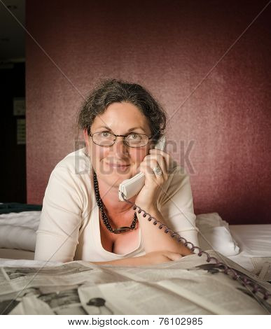 Woman On Telephone In Front Of Newspaper On Bed