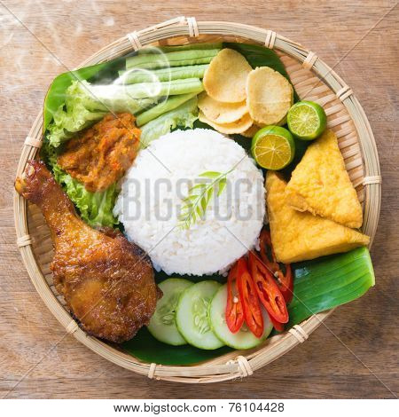 Famous traditional Indonesian food. Delicious nasi ayam penyet with sambal belacan. Fresh hot with steam smoke.