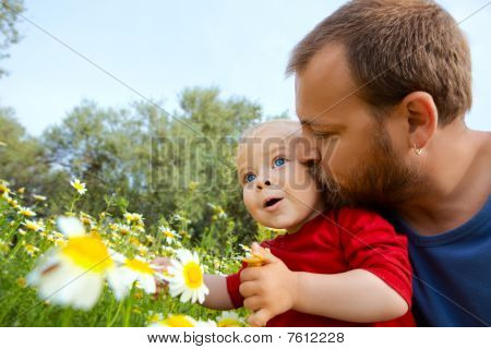 father in early thirties gives his son a kiss